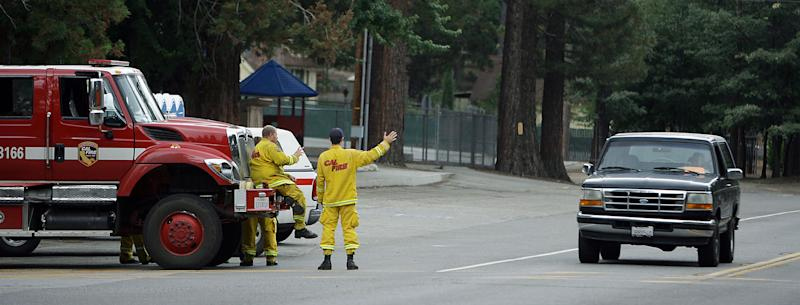 Cal Fire firefighters wave to residents returning to Idyllwild on Highway 243 after the evacuation order was rescinded in the areas affected by the Mountain Fire on Sunday, July 21, 2013. Thousands of people were allowed to return to their homes in Southern California mountain communities near Palm Springs on Sunday, after firefighters aided by heavy rain made substantial progress against a week-old wildfire that has burned across 42 square miles and destroyed seven homes. (AP Photo/The Press-Enterprise, Terry Pierson)
