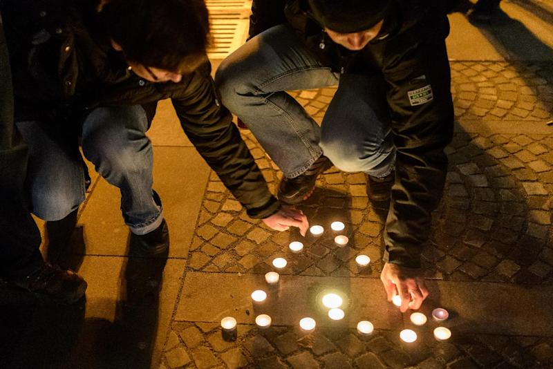 """Members of the """"Trans-Universal Zombie Church of the Blissful Ringing"""" light candles during their weekly service in front of the Slovenian parliament, the """"sanctuary of corruption"""", in Ljubljana, on November 19, 2014 (AFP Photo/Jure Makovec)"""