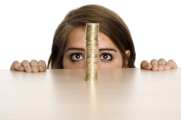 A teenage girl watching a stack of British Pound coins
