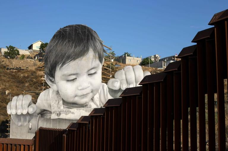 One-year-old Kikito peers over the wall at the US-Mexico border