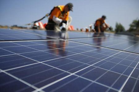 Vivint Solar technicians install solar panels on the roof of a house in Mission Viejo