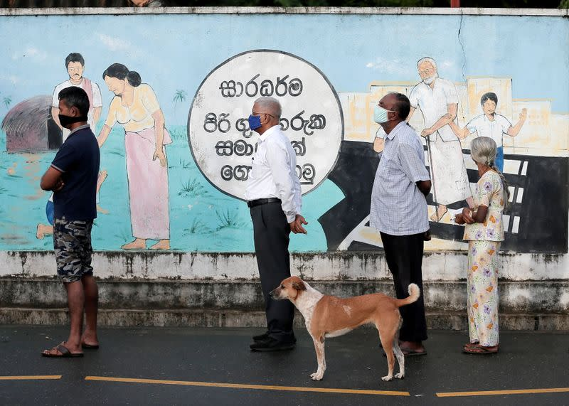 People wearing protective masks wait in a line outside a polling station as they prepare to cast their vote in Colombo