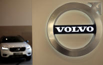 FILE - In this Feb. 6, 2020 file photo a Volvo car is parked behind the Volvo logo in the lobby of the company's corporate headquarters, in Brussels. Volvo says it will make only electric vehicles by 2030. But for those who want one, they will have to buy it online. The Swedish automaker said Tuesday, March 2, 2021, that it is phasing out the production of all cars with internal combustion engines — including hybrids. (AP Photo/Virginia Mayo, File)