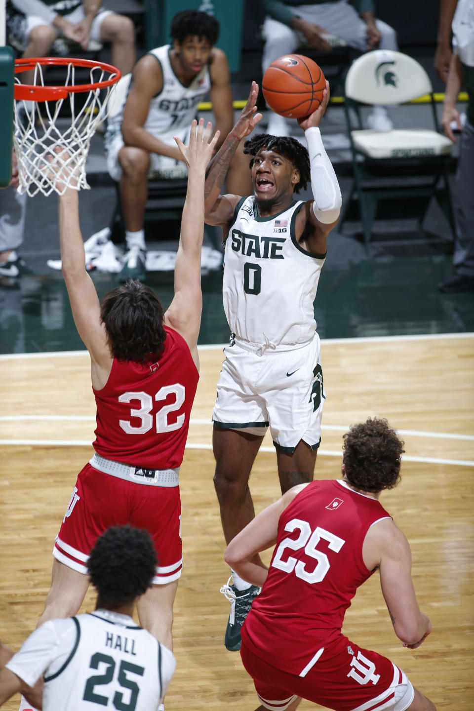 Michigan State's Aaron Henry (0) shoots against Indiana's Trey Galloway (32) and Race Thompson (25) during the second half of an NCAA college basketball game Tuesday, March 2, 2021, in East Lansing, Mich. Michigan State won 64-58. (AP Photo/Al Goldis)