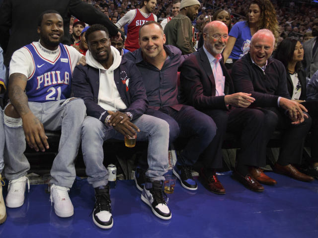 CORRECTS SPELLING TO JEFFREY, INSTEAD OF JEFFERY - Rapper Meek Mill, left, watches the game with actor Kevin Hart, center left, Philadelphia 76ers co-owner Michael Rubin, center, Pennsylvania Gov. Tom Wolf, center right, and Philadelphia Eagles owner Jeffrey Lurie, right, during the first half in Game 5 of a first-round NBA basketball playoff series against the Miami Heat, Tuesday, April 24, 2018, in Philadelphia. (AP Photo/Chris Szagola)