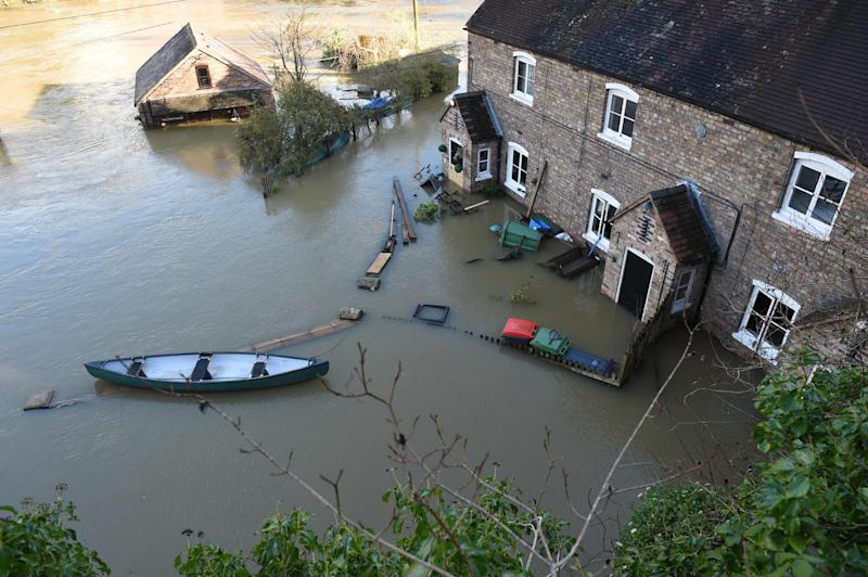 A picture shows a canoe outside a flooded home in Ironbridge (AFP via Getty Images)