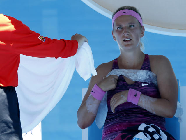 Victoria Azarenka of Belarus holds an ice pack around her during a break in her first round match against Johanna Larsson of Sweden at the Australian Open tennis championship in Melbourne, Australia, Tuesday, Jan. 14, 2014.(AP Photo/Eugene Hoshiko)