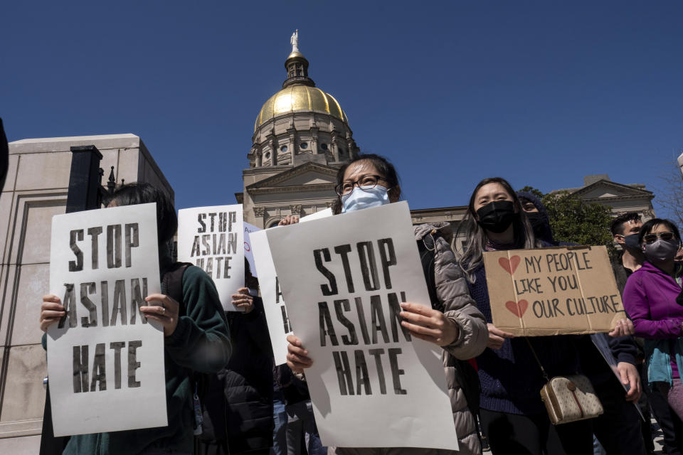 """People hold signs while participating in a """"stop Asian hate"""" rally outside the Georgia State Capitol in Atlanta on Saturday afternoon, March 20, 2021. (AP Photo/Ben Gray)"""