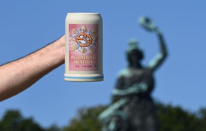 A man holds up the official 2020 Oktoberfest beer mug, in front of the Bavaria monument at Theresienwiese in Munich, southern Germany, the place of the yearly beer festival, on September 19, 2020. - The traditional Bavarian Oktoberfest beer festival would have started today, but it was canceled a few months ago due to the ongoing novel coronavirus Covid-19 pandemic.