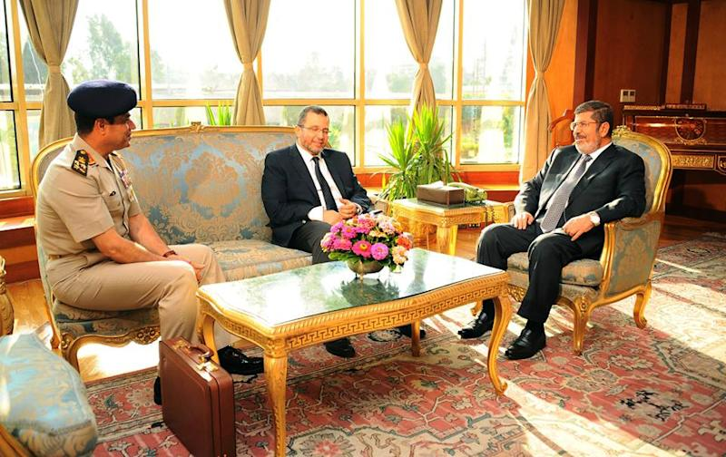"""FILE - In this file photo released by the Egyptian Presidency Monday, July 1, 2013, Egyptian President Mohammed Morsi, right, meets with Prime Minister Hesham Kandil, center, and Egyptian Minister of Defense, Lt. Gen. Abdel-Fattah el-Sissi, left in Cairo, Egypt. """"Over my dead body!"""" Mohammed Morsi told his army chief who came to him asking the Islamist president to step down on his own and not resist a military ultimatum and the demands of giant crowds out in the streets. Morsi found himself isolated, with trusted aides abandoning him, and in the end, the ring of Presidential Guards protecting him simply stepped away to allow the military to take him under its custody, according to army, security and Brotherhood officials giving The Associated Press an account of his last hours.(AP Photo/Egyptian Presidency, File)"""