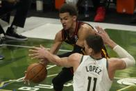 Atlanta Hawks' Trae Young tries to pass around Milwaukee Bucks' Brook Lopez during the first half of Game 2 of the NBA Eastern Conference basketball finals game Friday, June 25, 2021, in Milwaukee. (AP Photo/Morry Gash)