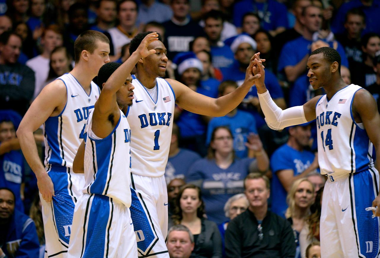 DURHAM, NC - DECEMBER 28: Marshall Plumlee #40, Quinn Cook #2, Jabari Parker #1 and Rasheed Sulaimon #14 of the Duke Blue Devils celebrate during their game against the Eastern Michigan Eagles at Cameron Indoor Stadium on December 28, 2013 in Durham, North Carolina. Duke won 82-59. (Photo by Grant Halverson/Getty Images)