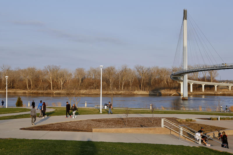 In this April 6, 2020 photo, residents stroll along the Missouri River in Omaha, Neb., as Council Bluffs, Iowa, is seen across the river. As most governors have imposed stay-at-home orders that public health officials say are essential to slowing the spread of the new coronavirus, leaders in a handful of states have steadfastly refused to take the action, arguing it's unneeded and potentially harmful. (AP Photo/Nati Harnik)