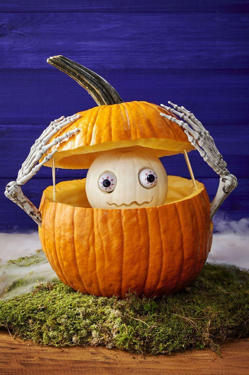 <p>With a large serrated knife, cut off top ⅓ of large orange pumpkin and hollow out. Then hollow out bottom part too, and on each side, cut a hole halfway down; push skeleton arms through. Cut divots in bottom's base to keep arms steady. </p><p>For skull, trace plastic Halloween eyeballs on a small white pumpkin; hollow inside traced circles with melon baller, push eyeballs into holes, and then carve a mouth. Position stemless medium white pumpkin inside bottom section of big pumpkin for body; top with skull. Secure top and bottom sections of large orange pumpkin along back and sides with wood skewers. Arrange skeleton hands over top.</p>