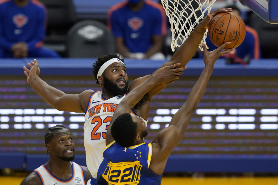 New York Knicks center Mitchell Robinson (23) defends against a shot by Golden State Warriors forward Andrew Wiggins (22) during the second half of an NBA basketball game in San Francisco, Thursday, Jan. 21, 2021. (AP Photo/Jeff Chiu)