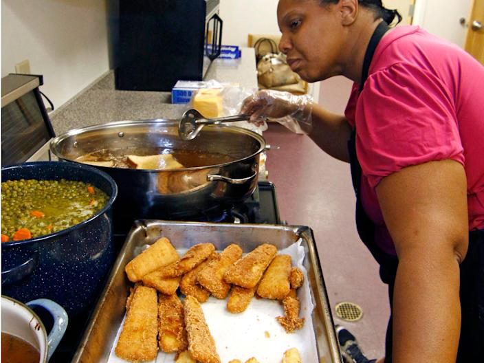 Earnestine Nelson, chief cook for the Alpha and Omega Church's free summer meals program for children and teens, checks the progress of her peas and carrots while frying fish fillets and tater tots for lunch, June 12, 2009, in Jackson, Mississippi.