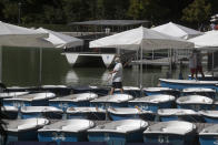 "A worker prepares pleasure boats to be rented in the Retiro park, Madrid, Spain, Sunday, Aug. 23, 2020. Spain's top pandemic expert, Fernando Simon, has warned this week that ""things are not going well"" regarding the increase of infections that the country is seeing. (AP Photo/Paul White)"