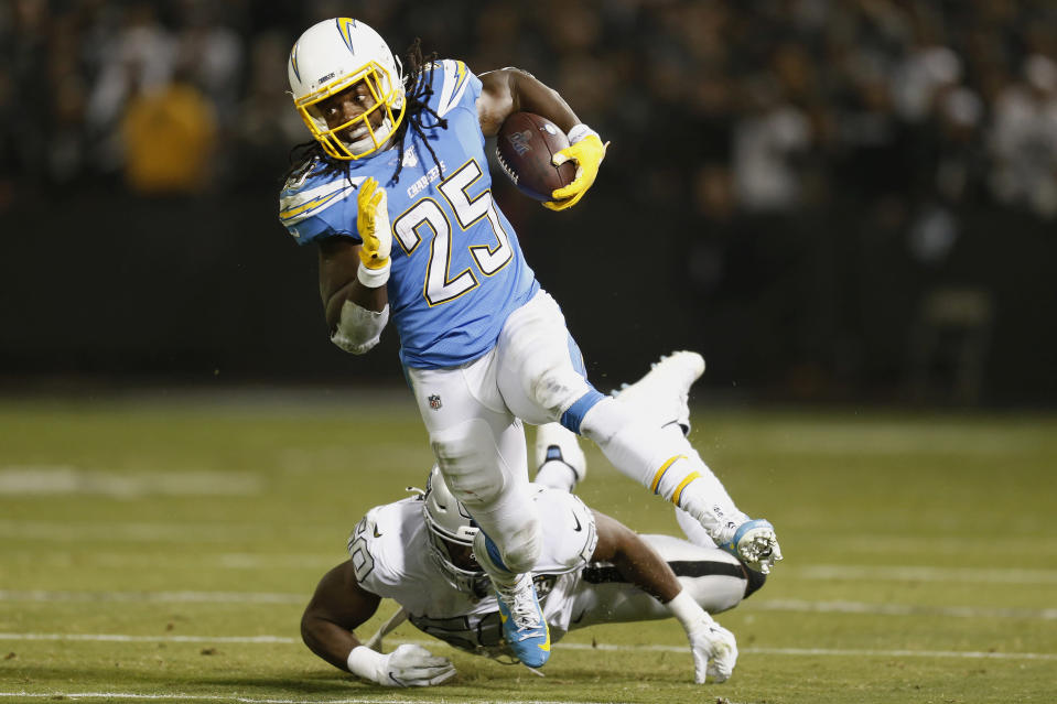 Los Angeles Chargers running back Melvin Gordon (25) runs past Oakland Raiders linebacker Nicholas Morrow during the first half of an NFL football game in Oakland, Calif., Thursday, Nov. 7, 2019. (AP Photo/D. Ross Cameron)