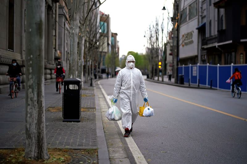 Man wearing a hazmat suit walks on a street in Wuhan