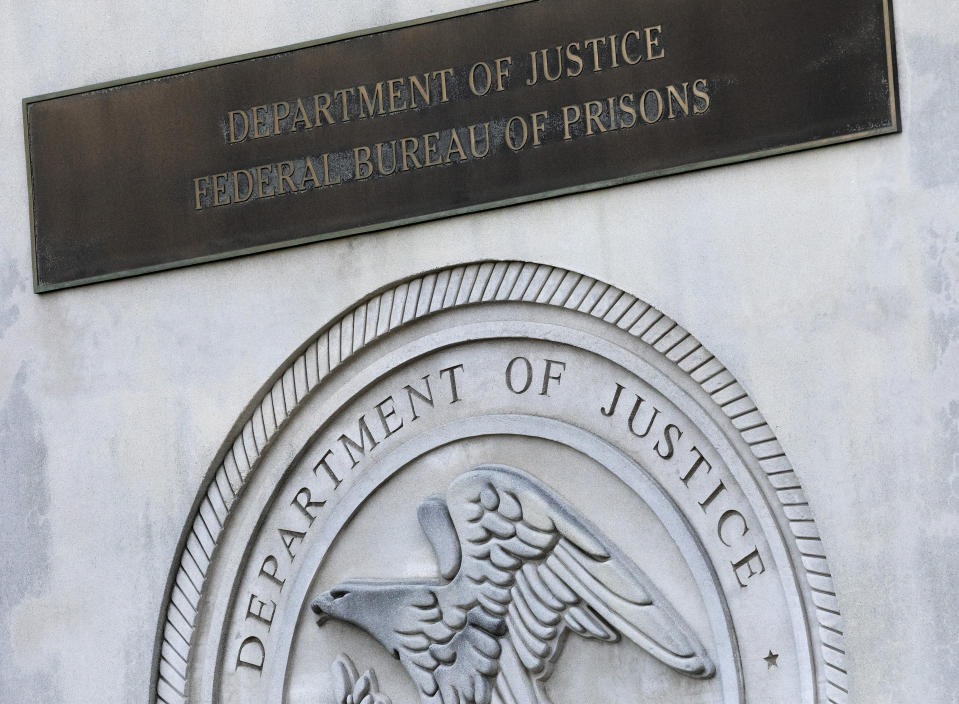 FILE - In this July 6, 2020, file photo a sign for the Department of Justice Federal Bureau of Prisons is displayed at the Metropolitan Detention Center in the Brooklyn borough of New York. Over the past 18 months, 29 prisoners have escaped from federal lockups across the U.S. - and nearly half still have not been caught. At some of the institutions, cells are left unlocked, security cameras are broken and officials sometimes don't notice an inmate missing for hours. (AP Photo/Mark Lennihan, File)
