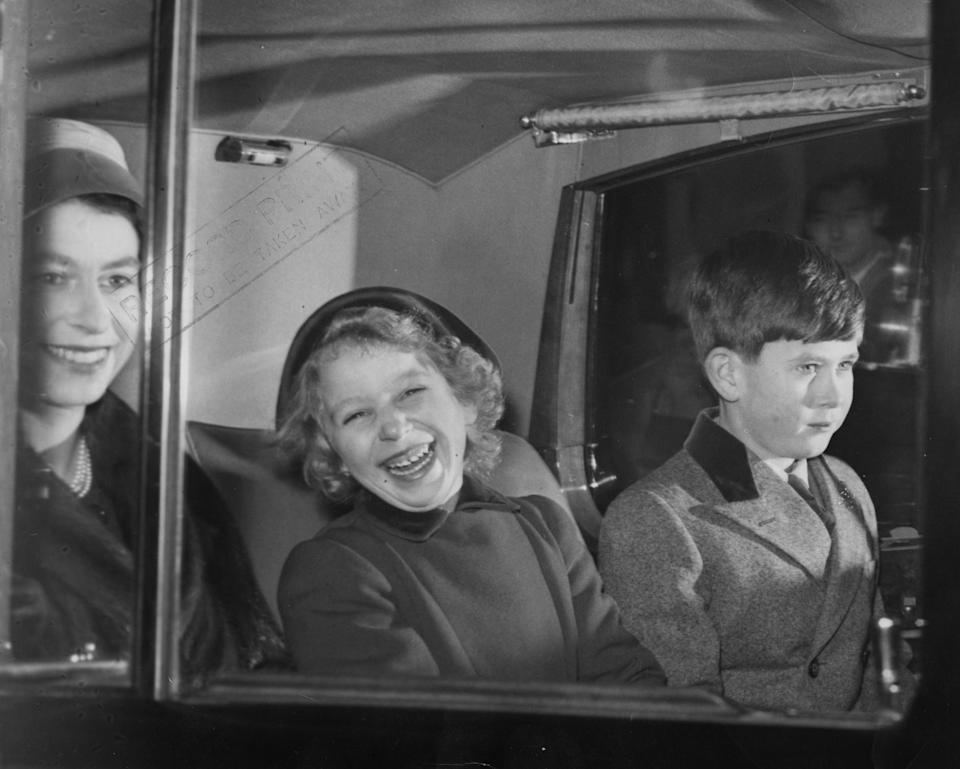A laughing Princess Anne sits with her mother, the Queen, and Prince Charles in a car taking them from Buckingham Palace on their way to Sandringham for the Christmas holidays in 1956. (PA)
