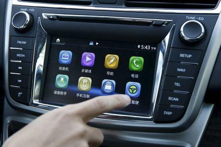 An engineer activates a button for the self driving mode of Changan Automobile's self-driving car, a modified Raeton sedan, during a test drive on a highway in Beijing, April 16, 2016. REUTERS/Kim Kyung-Hoon