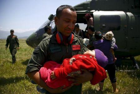 A Nepalese army personnel holds the baby of an earthquake victim after being airlifted from Sindhupalchok District to Kathmandu