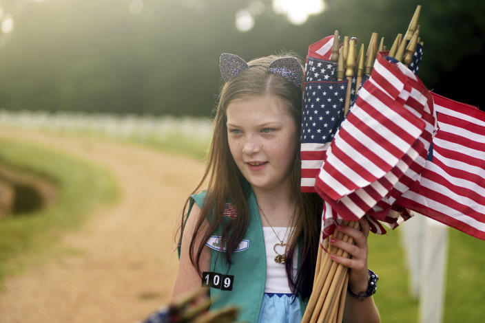 <p>Girl Scout Caitlyn Hootsell, 10, carries a bundle of U.S. flags, Saturday, May 26, 2018 for placement in front of tombstones at the Natchez National Cemetery in Natchez, Miss., as the community honors those who died in service to their country. (Photo: Nicole Hester/The Natchez Democrat via AP) </p>