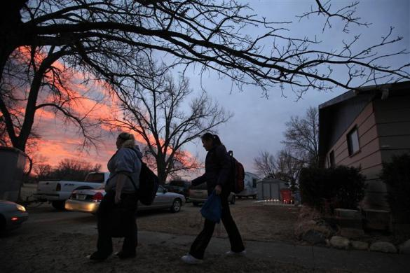 Amy Wang (R), a foreign exchange student from Shenyang, China, leaves her host family's house with friend Trinity Novy for a ride to school in Marietta, South Dakota February 14, 2012.