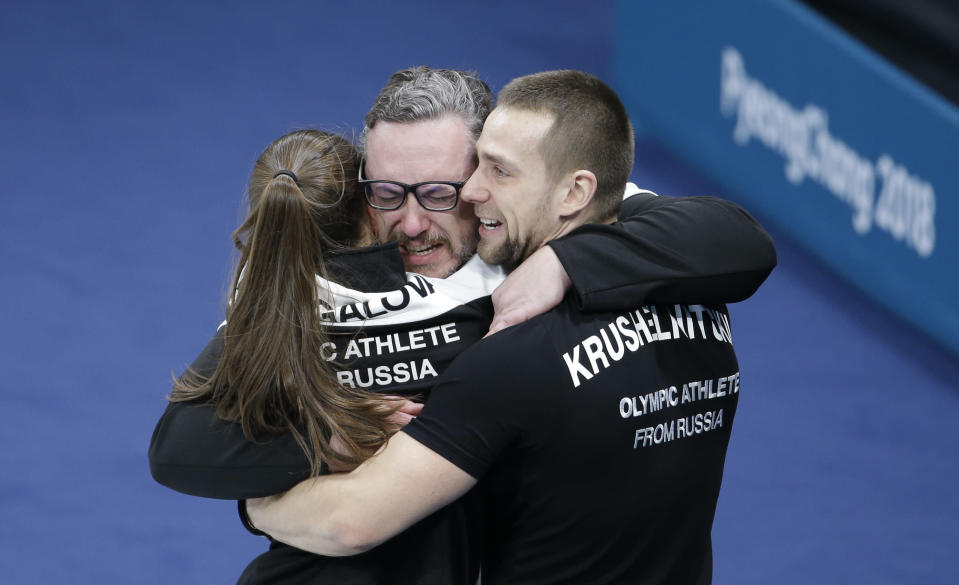 <p>Russian athletes Anastasia Bryzgalova, left, and Aleksandr Krushelnitckii, right, embrace their coach Vasily Gudin after winning the mixed doubles bronze medal curling match against Norway's Kristin Skaslien and Magnus Nedregotten at the 2018 Winter Olympics in Gangneung, South Korea, Tuesday, Feb. 13, 2018. (AP Photo/Natacha Pisarenko) </p>
