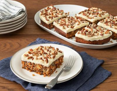 Carrot Cake includes a moist carrot cake baked with coconut, pineapple, walnuts, cinnamon and vanilla, then topped with a generous spread of cream cheese icing and chopped pecans.