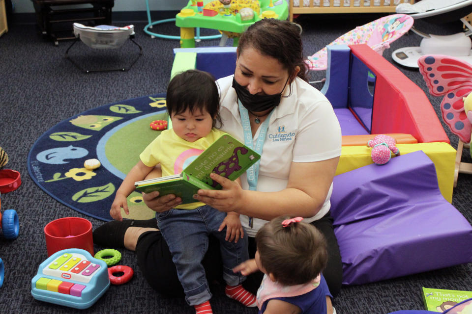 This May 4, 2021 image shows teacher Graciela Olague-Barrios reading to two infants at Cuidando Los Ninos in Albuquerque, N.M. The charity provides housing, child care and financial counseling for mothers, all of whom will benefit from expanded Child Tax Credit payments that will start flowing in July to roughly 39 million households. (AP Photo/Susan Montoya Bryan)