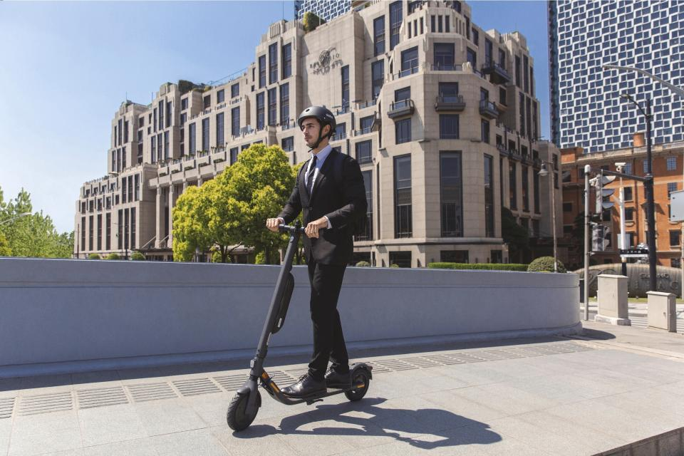 A man wearing a business suit while riding a Segway Scooter through a city