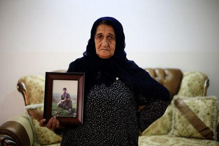 A woman holds a picture of her son, who was a victim of the 1988 chemical attack, as she poses for the camera in the Kurdish town of Halabja, Iraq September 22, 2017. REUTERS/Thaier Al-Sudani
