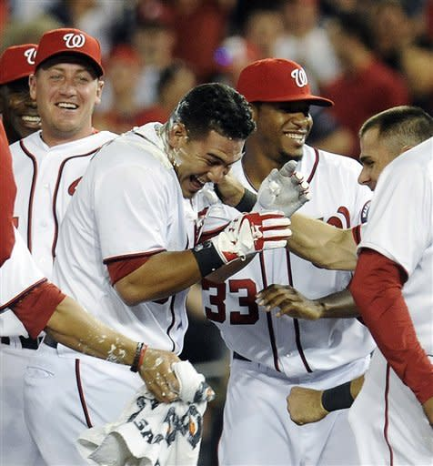 Washington Nationals' Wilson Ramos, center, celebrates with teammates, including Edwin Jackson (33), after hitting the game-winning hit scoring Steve Lombardozzi in the 11th inning to defeat the Philadelphia Phillies 4-3 during their baseball game at Nationals Park, Friday, May 4, 2012, in Washington. (AP Photo/Richard Lipski)