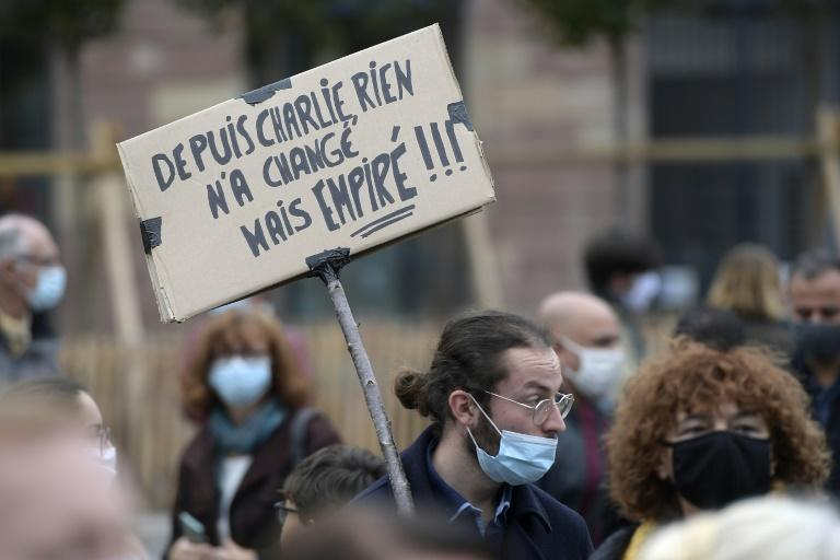 """A man holds a placard reading """"Nothing changed since Charlie"""" at a demonstration for beheaded schoolteacher Samuel Paty"""