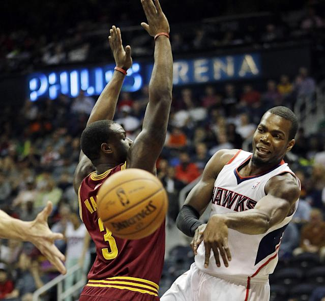 Atlanta Hawks' Paul Millsap, right, passes the ball behind the back of Cleveland Cavaliers' Dion Waiters in the first quarter of an NBA basketball game, Friday, April 4, 2014, in Atlanta. (AP Photo/David Goldman)