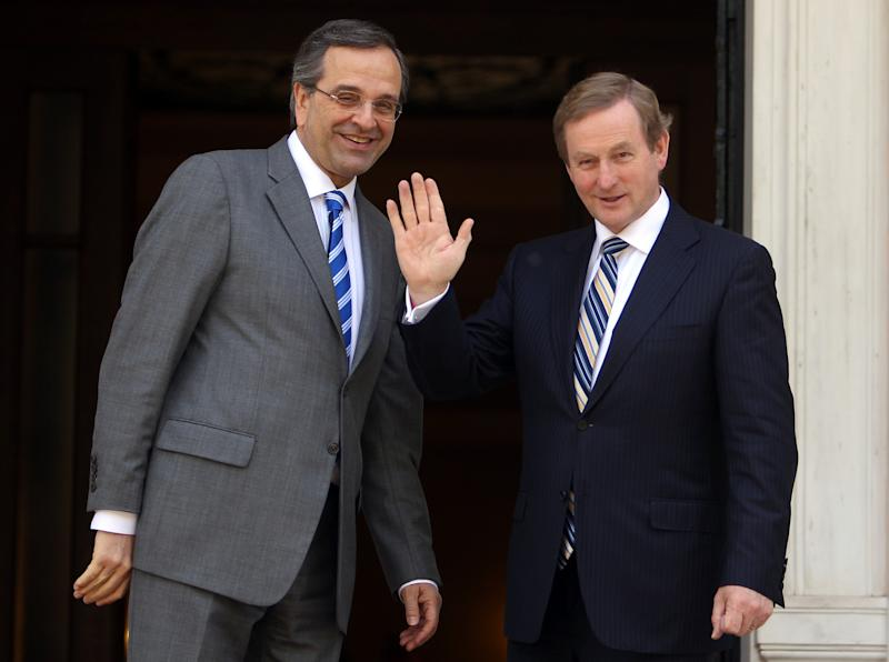 """Greece's Prime Minister Antonis Samaras, left and his Irish counterpart Enda Kenny wave to the media prior to their meeting at Maximos Mansion in Athens, Thursday, May 23, 2013. Samaras said that Greece would follow the """"same successful model"""" as Ireland both of the EU presidency and to exit the crisis. Ireland's EU presidency will finish in the end of June. Greece is scheduled to take over the EU's rotating six-month presidency in January 2014. (AP Photo/Thanassis Stavrakis)"""