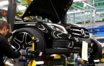 FILE PHOTO: An employee of German car manufacturer Mercedes Benz installs wheel at a A-class model at the production line at the Daimler factory in Rastatt