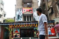 A commuter passes by a poster of Bollywood actor Amitabh Bachchan at the gate of All Bengal Amitabh Bachchan Fan Club in Kolkata ,India on July 12, 2020. Bollywood megastar Amitabh Bachchan, 77, tested positive for COVID-19 on July 11 and was admitted to hospital in Mumbai, with his actor son Abhishek -- who also announced he had the virus -- saying both cases were mild. (Photo by Debajyoti Chakraborty/NurPhoto via Getty Images)