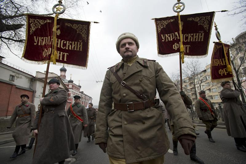 Pro-Kremlin demonstrators dressed in WWII army uniforms and carrying replicas of Soviet Army WWII banners reading, Ukrainian Front, march in central Moscow, Russia, Sunday, March 2, 2014 to express support for the latest developments in Russian-Ukrainian relations. Banners are those of units that were liberating Ukraine from Nazi occupation during WWII. (AP Photo/Pavel Golovkin)