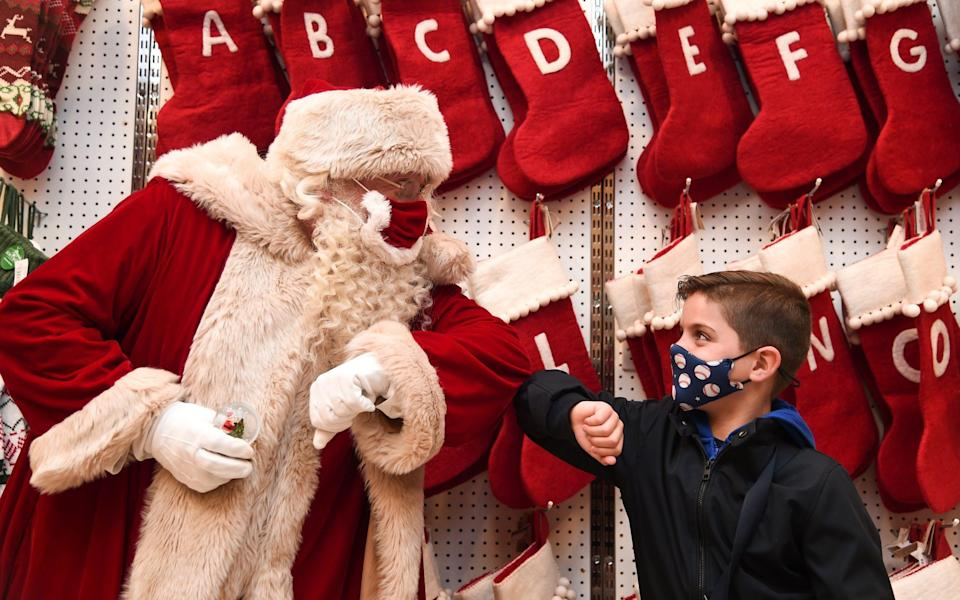 """LONDON, ENGLAND - OCTOBER 12: Santa Claus greets Jaythan Corbacho with an elbow bump during the Selfridges 2020 Christmas Shop """"Once upon a Christmas"""" photocall at Selfridges, Oxford Street on October 12, 2020 in London, England. (Photo by Eamonn M. McCormack/Getty Images)"""
