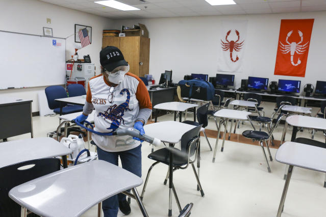 Custodial staff use an electrostatic Clorox sprayer to disinfect a classroom on March 11, 2020, at Brownsville Early College High School in Brownsville, Texas. (Denise Cathey/The Brownsville Herald via AP)