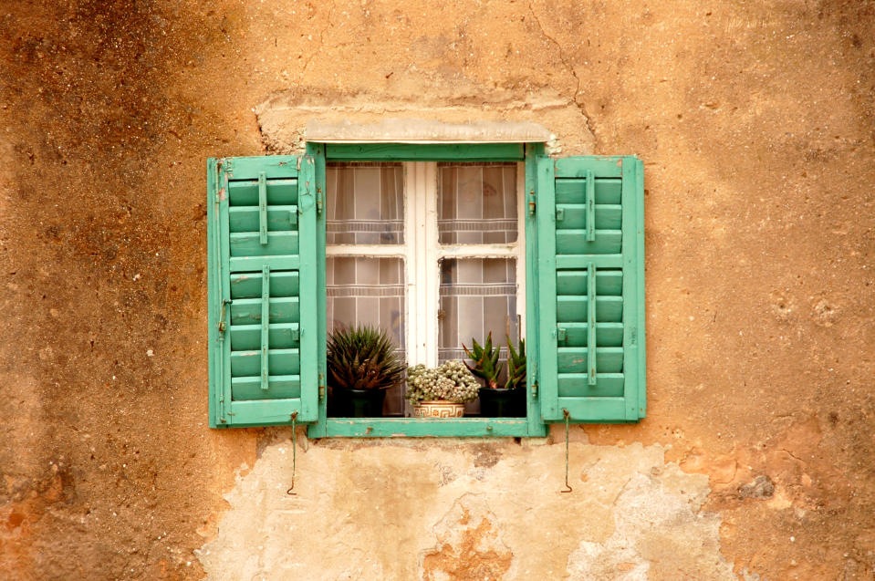 an old house window decorated with flowers