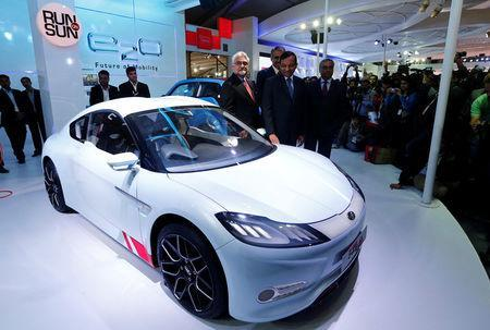 FILE PHOTO: Pawan Goenka (C), president of Mahindra's automotive and farm equipment sectors, stands next to Mahindra's concept electric sports car 'Halo' after its unveiling during the Indian Auto Expo in Greater Noida, on the outskirts of New Delhi, India, February 6, 2014. REUTERS/Adnan Abidi/File photo
