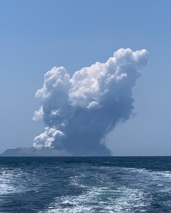 The White Island volcano shown erupting from a distance. Source: AAP