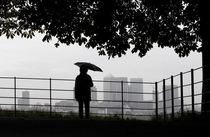 A man holds an umbrella as he looks out at London's Canary Wharf financial district from Greenwich park