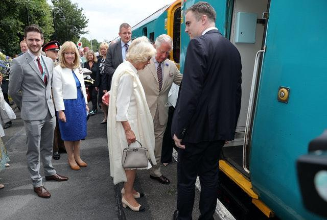 The Prince of Wales helps the Duchess of Cornwall board a train during a visit to Llandovery Railway Station to mark the 150th anniversary of the Heart of Wales railway line. Andrew Matthews/PA Wire