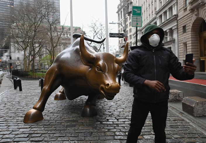 A man wearing a face mask takes a selfie at the Charging Bull statue on March 23, 2020 near the New Stock Exchange in New York City. - Wall Street fell early March 23, 2020 as Congress wrangled over a massive stimulus package while the Federal Reserve unveiled new emergency programs to boost the economy including with unlimited bond buying. About 45 minutes into trading, the Dow Jones Industrial Average was down 0.6 percent at 19,053.17, and the broad-based S&P 500 also fell 0.6 percent to 2,290.31 after regaining some ground lost just after the open. (Photo by Angela Weiss / AFP) (Photo by ANGELA WEISS/AFP via Getty Images)