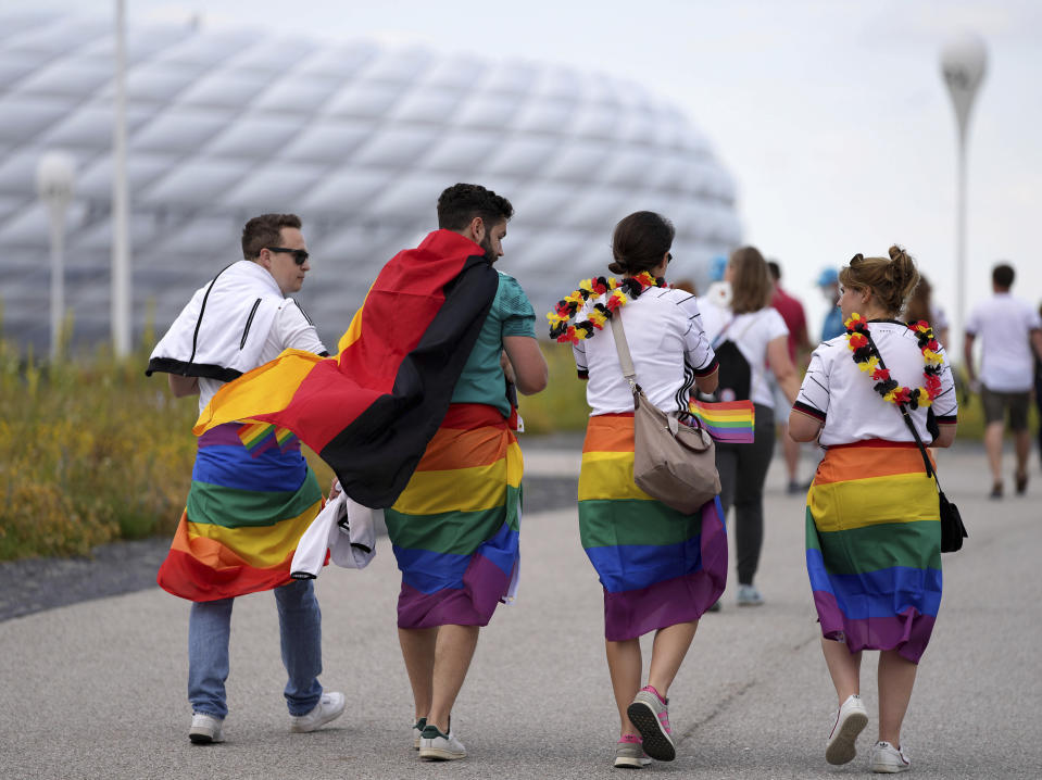 Football supporters are seen with LGBT pride flags on their way to the stadium before the Euro 2020 soccer championship group F match between Germany and Hungary at the Allianz Arena in Munich, Germany,Wednesday, June 23, 2021. (AP Photo/Matthias Schrader)